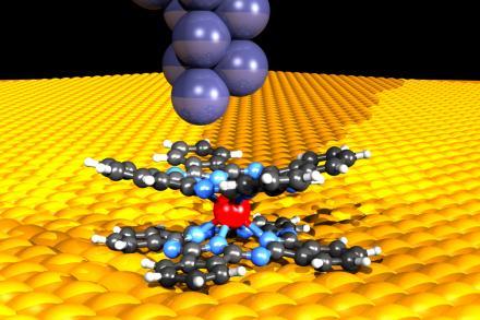 Die Spitze eines Rastertunnelmikroskops(oben) leiteten elektrischen Strom durch ein magnetisches Doppeldeckermolekül auf einer Kupferschicht. Im Zentrum befindet sich ein Neodym-Atom (rot). Bild: Forschungszentrum Jülich