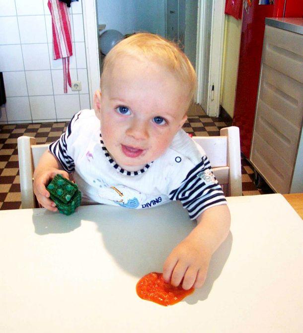 """Der 12 Monate alte Finn nimmt etwas Karottenbrei mit dem Pinzettengriff auf und führt ihn anschließend zum Mund. Möglicherweise bleibt als Erinnerung eine tiefe Befriedigung beim Ausführen der auf dem Tablet """"Pinch-to-Zoom"""" genannten Geste zurück (Bild: Georg peez)."""
