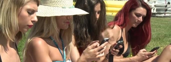Mitarbeiterinnen von Spinali Design mit Smartphones am Strand (Screenshot: ITespresso bei Dailymotion)
