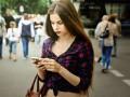 Junge Frau mit Smartphone im Straßenverkehr (Bild: Shutterstock)