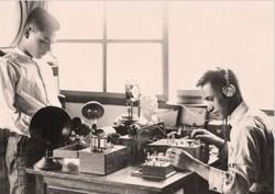 """Sharp-Gründer Tokuji Hayakawa (rechts), beim Test von Radiogeräten Mitte der Zwanziger Jahre. Der Erfinder hatte zuvor einen stets scharfen, mechanischen Stift (daher der Firmenname """"Sharp"""") entwickelt und auf den Markt gebracht und erweiterte das Geschäft dann als erster Anbieter von Radios in Japan in den Elektronikbereich (Bild: Sharp)."""