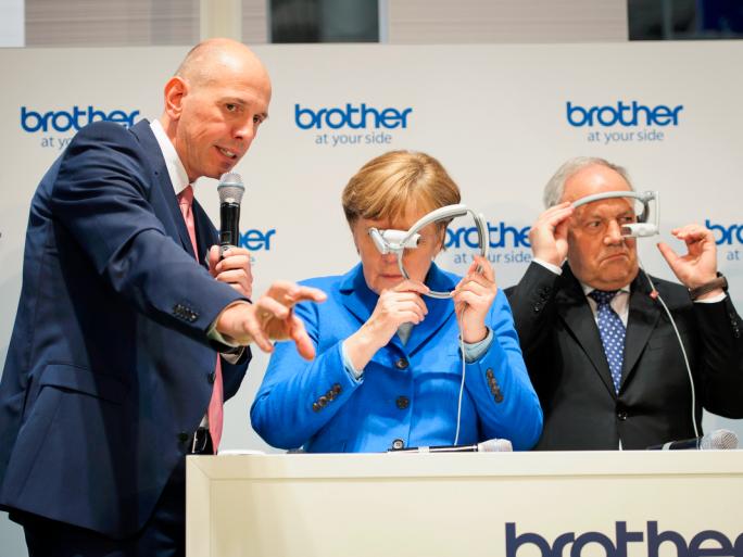 """Bild mit Symbolcharakter: Auf der diesjährigen CeBIT erklärt Matthias Kohlstrung, Geschäftsführer von Brother Deutschland, Kanzlerin Angela Merkel die Augmented-Reality-Brille """"AirScouter"""" seines Unternehmens – doch die Kanzlerin ist noch etwas ratlos, was sich mit der neuen Technologie anfangen lässt. (Bild: Bundesregierung/Güngör)"""